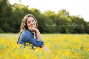 senior girl sitting in a field of yellow flowers