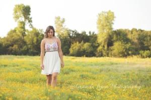 senior girl walking thru a field of yellow flowers