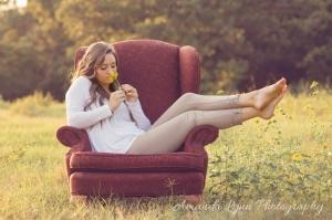 senior girl sitting in chair in open field