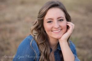 senior girl sitting in hay pasture in oklahoma