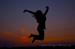 senior girl silhouette jumping at sunset