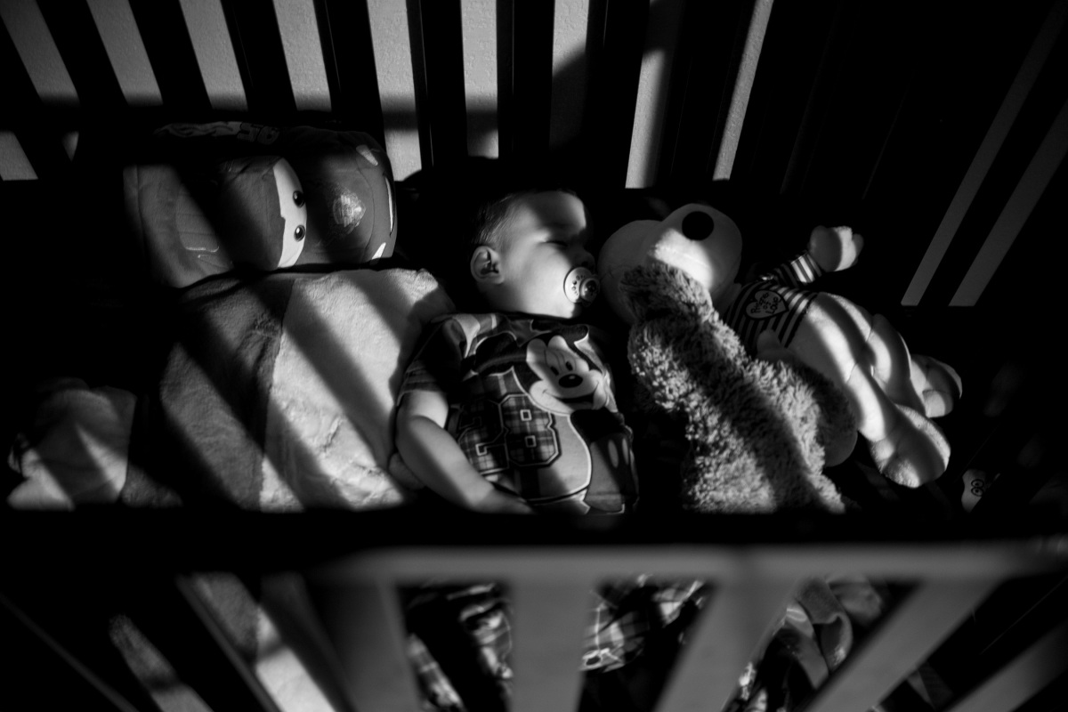 little boy sleeping in crib with stuffed animals in harrah oklahoma