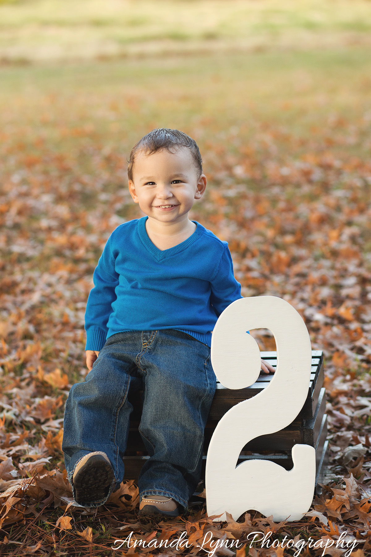 little boy wearing blue sweater sitting on crate with big number 2 harrah oklahoma