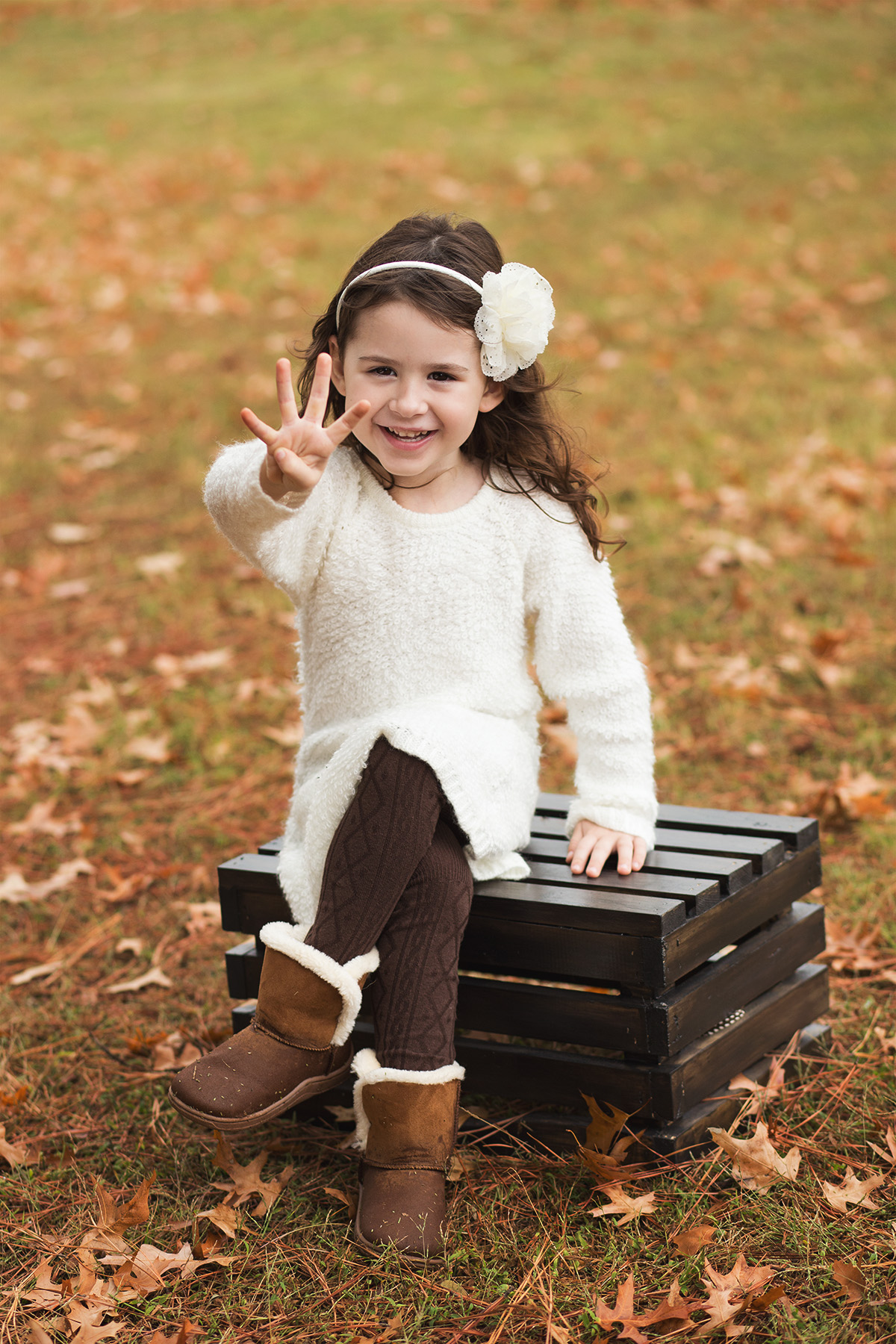 little girl wearing sweater and head band sitting on wood crate harrah oklahoma