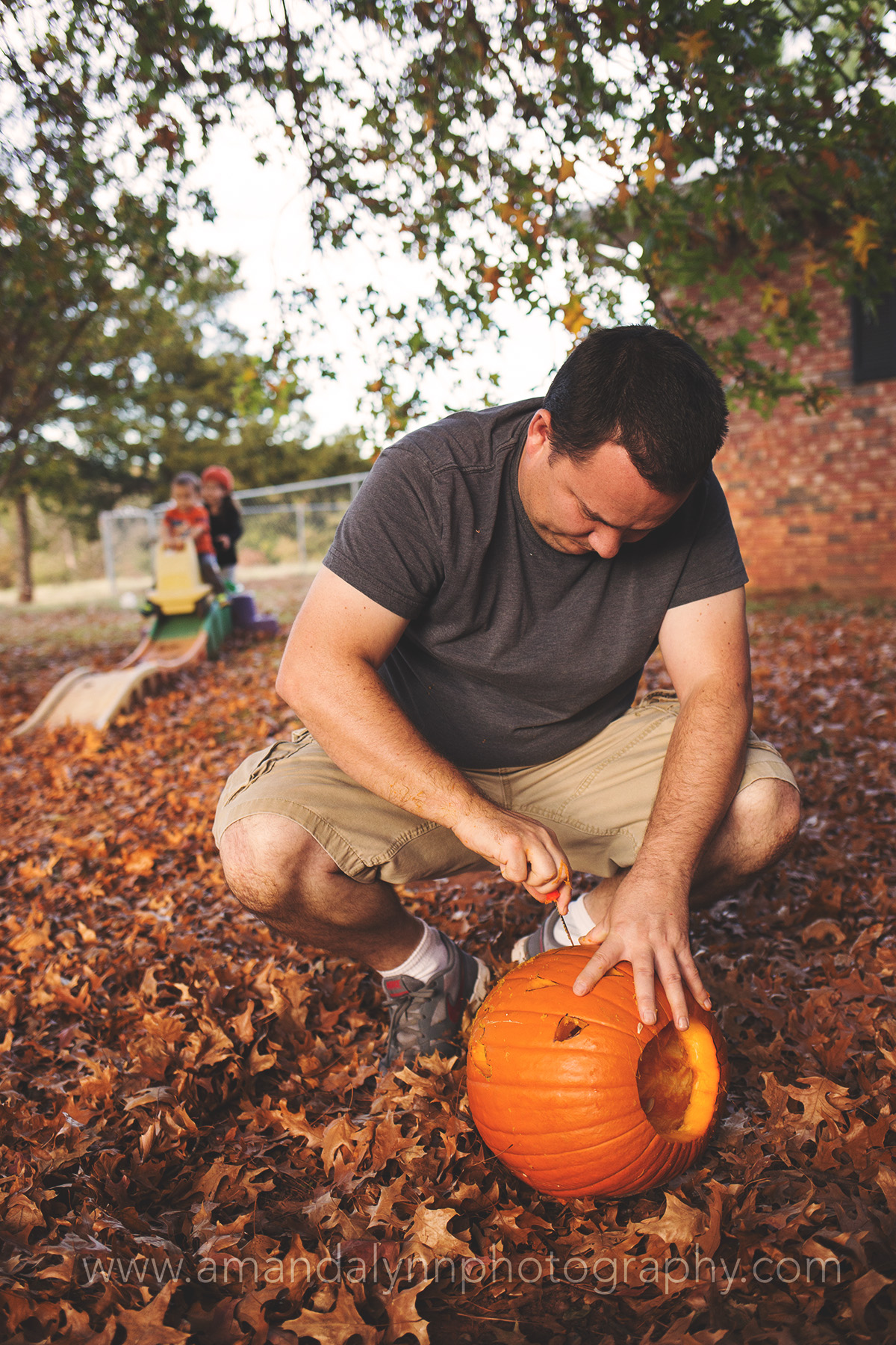 Dad Carving Pumpkins while children play