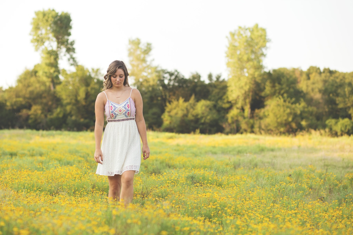 2016 senior girl walking thru field of yellow flowers  harrah oklahoma
