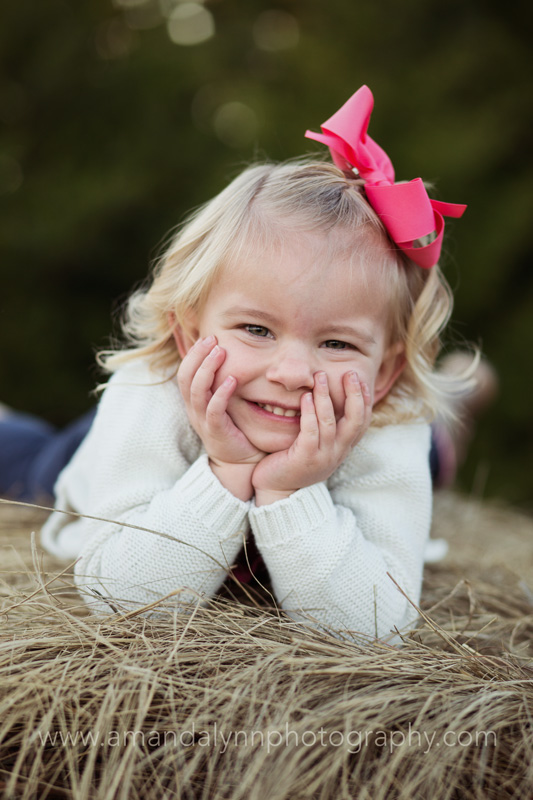 little girl laying on hay bale in stillwater oklahoma
