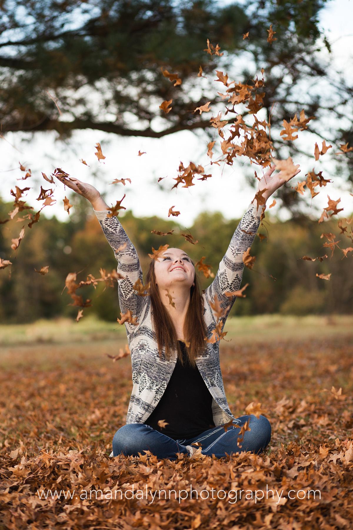 senior girl throwing leaves in the air in harrah oklahoma