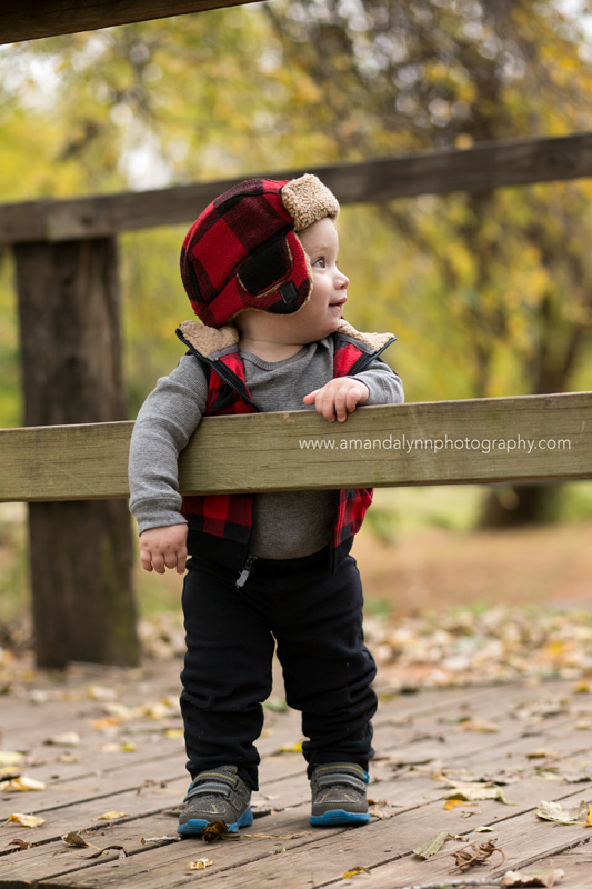 little boy wearing plaid hat standing on bridge in midwest city oklahoma