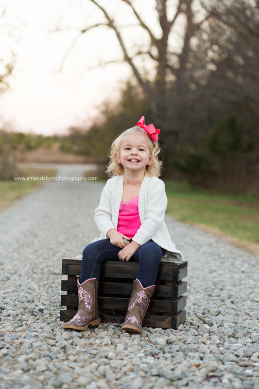 little girl sitting on wooden crate on gravel road in stillwater oklahoma