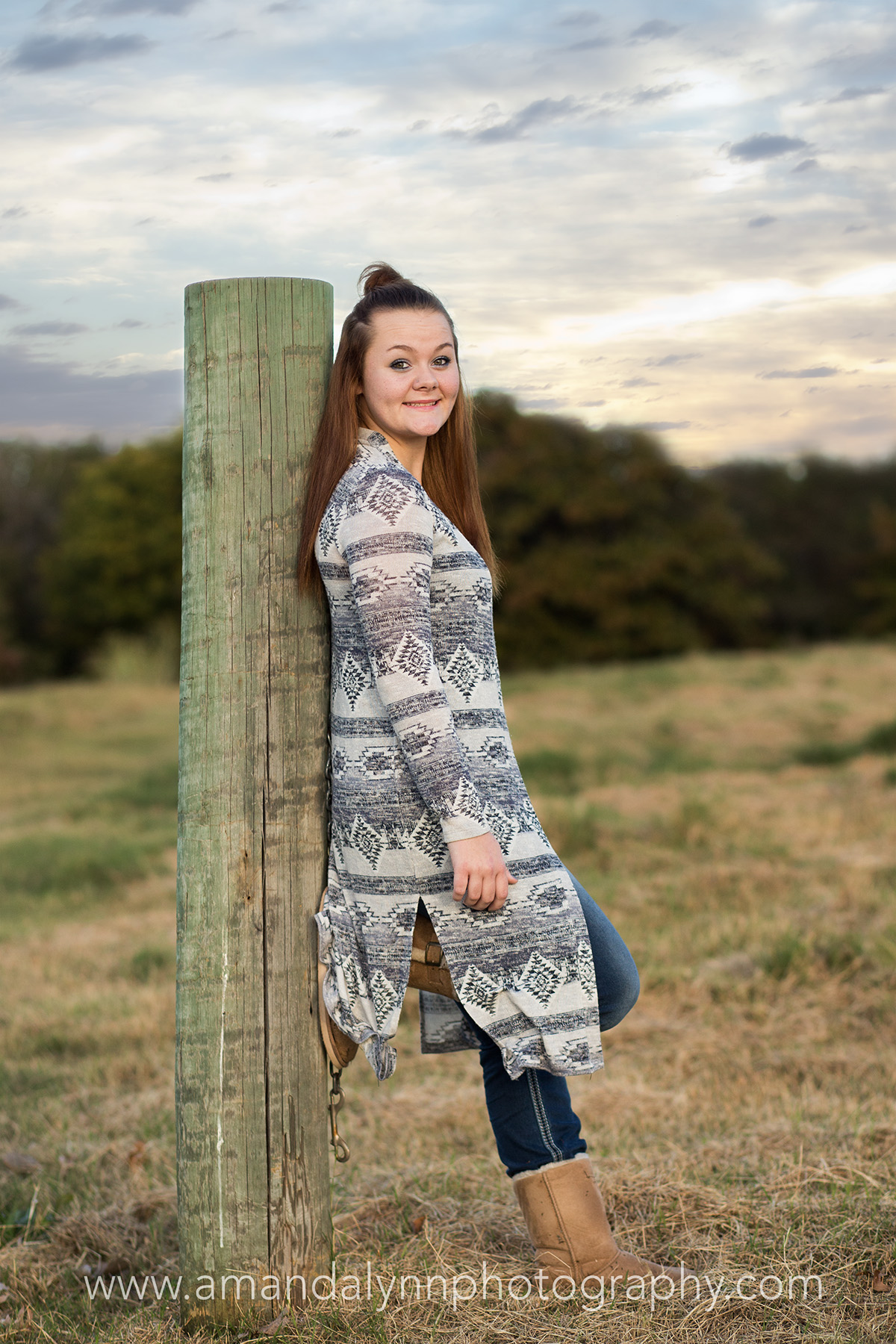 senior girl leaning on fence post in harrah oklahoma