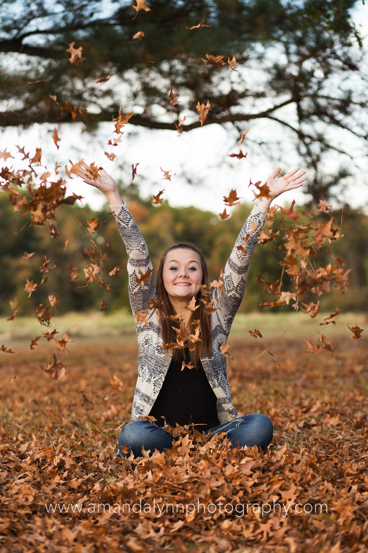 Senior girl throwing leaves into the air in harrah oklahoma