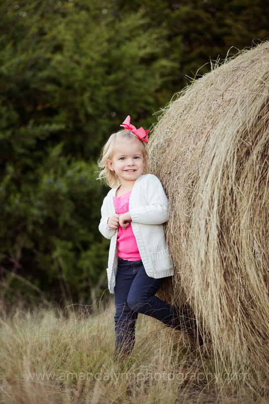 little girl leaning on hay bale in stillwater oklahoma