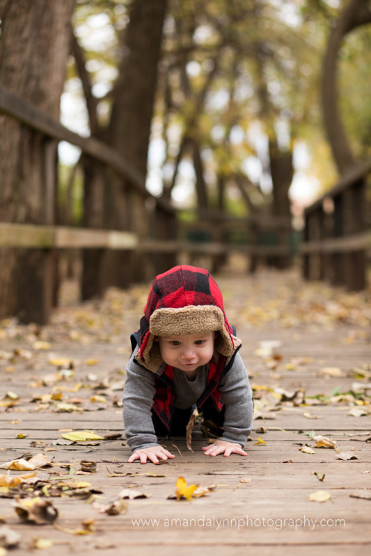 little boy wearing plaid hat crawling on bridge in midwest city oklahoma
