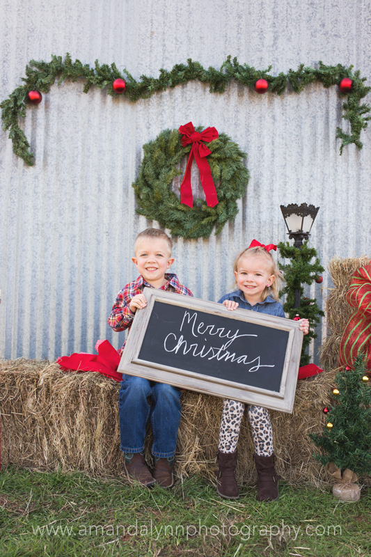 siblings holding christmas sign in harrah oklahoma
