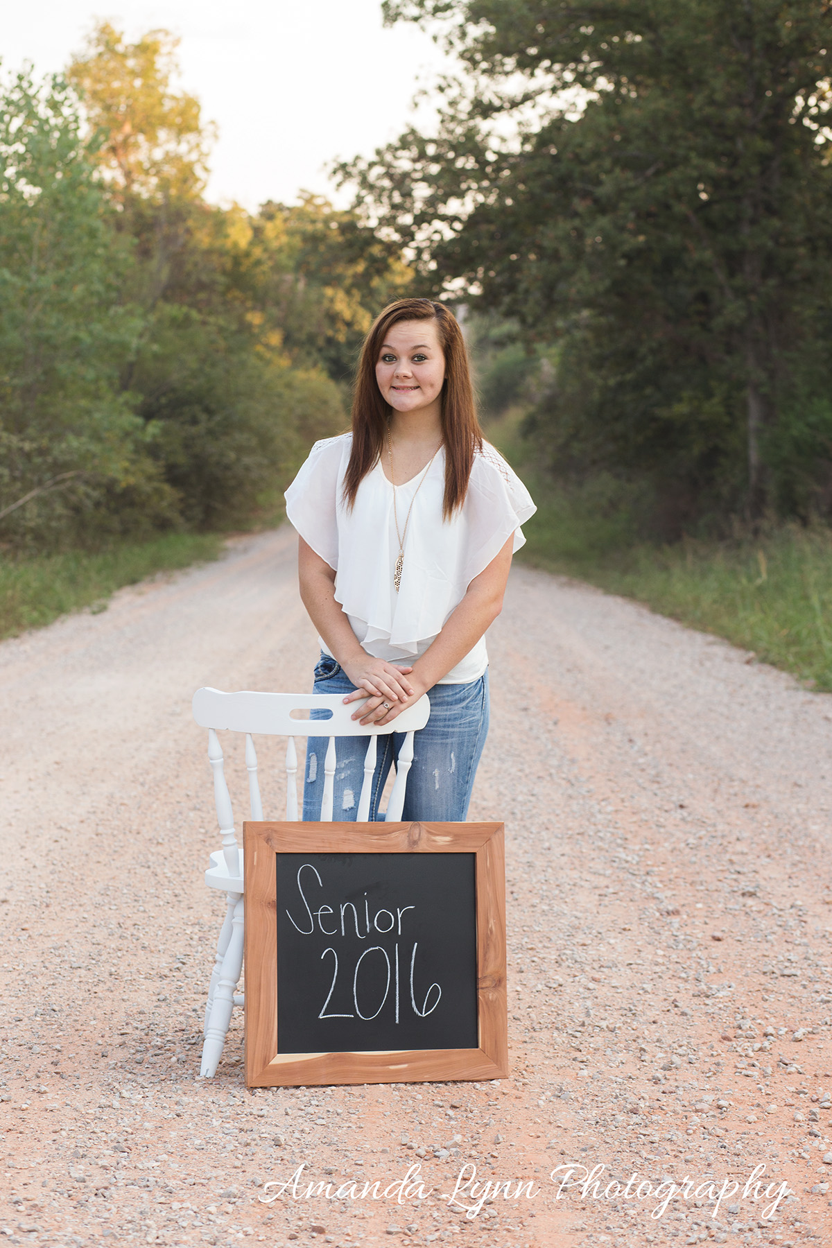 senior girl standing on dirt road with chalk board
