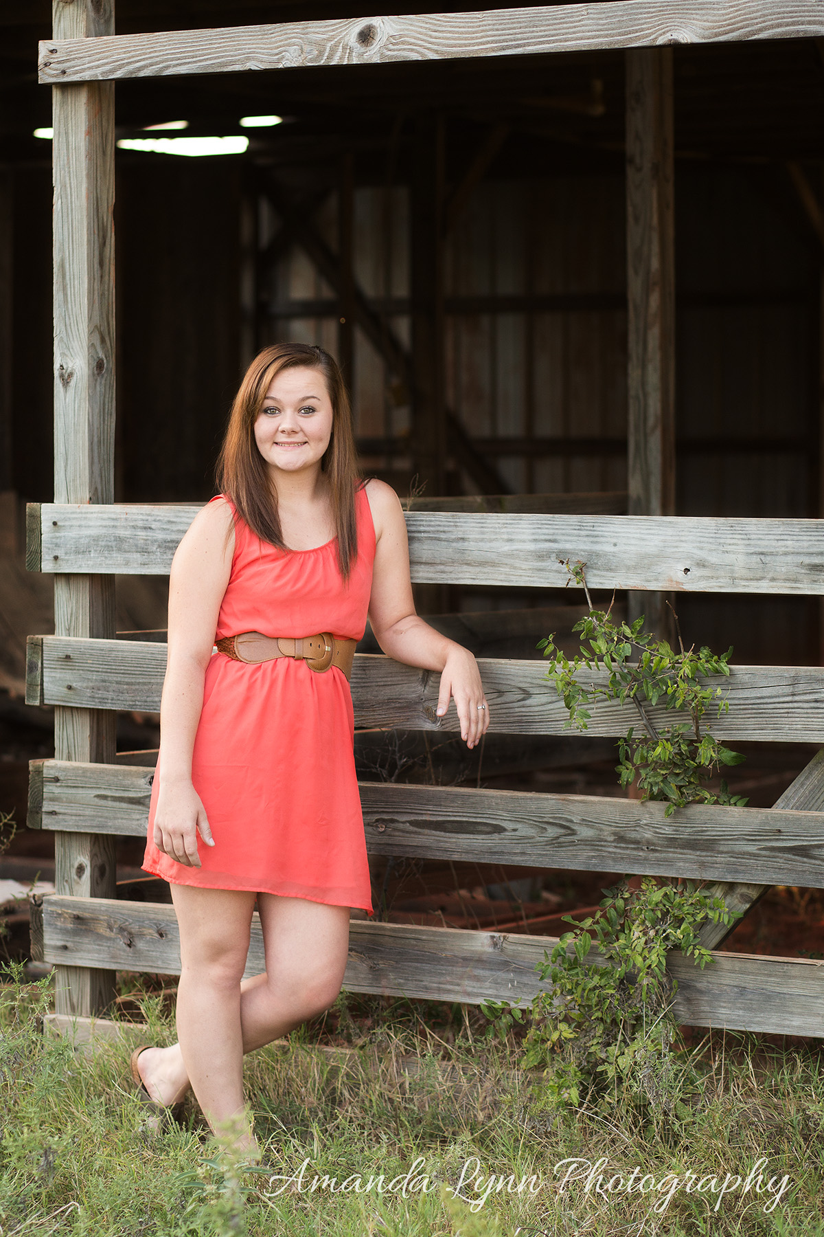 senior girl wearing orange dress leaning on old barn in harrah oklahoma