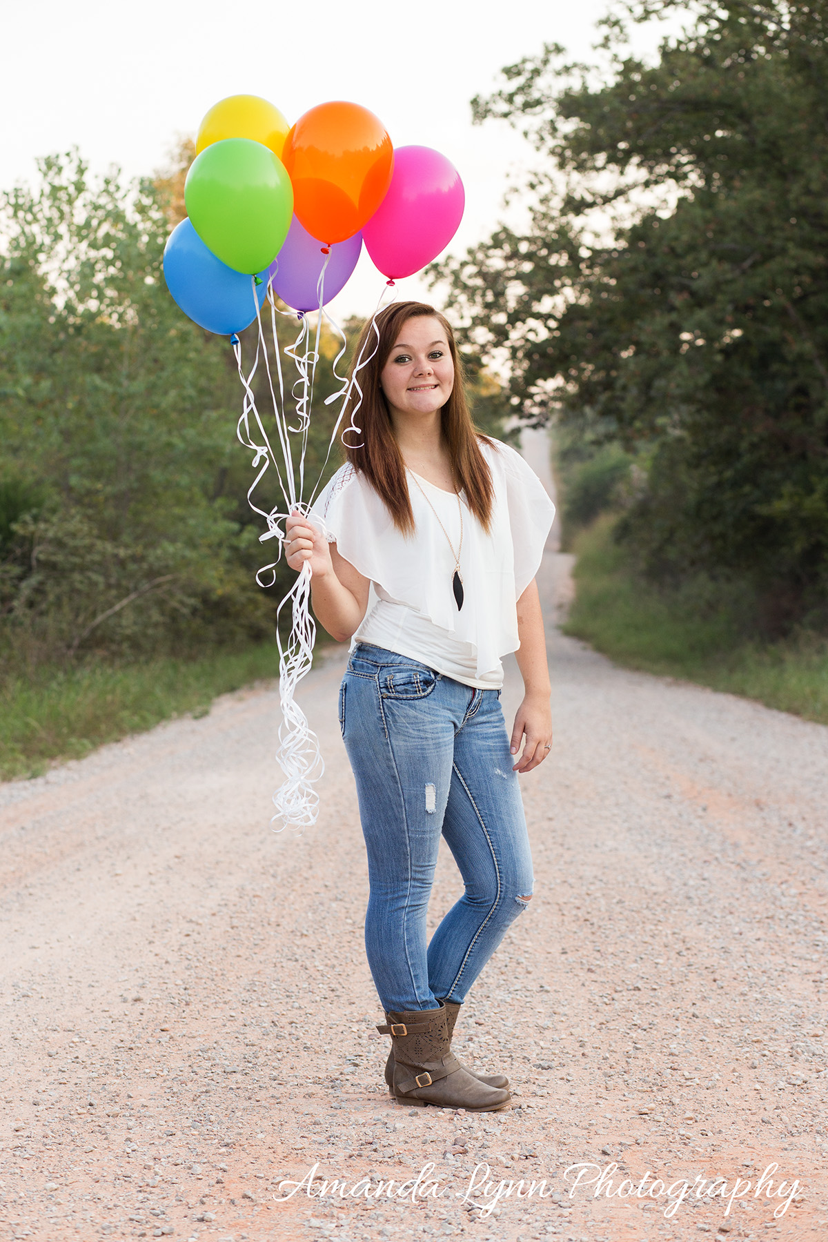 senior girl standing on dirt road holding balloons in harrah oklahoma