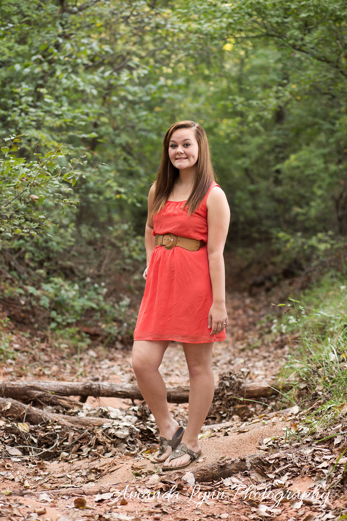 senior girl wearing orange dress standing in old creek in harrah oklahoma
