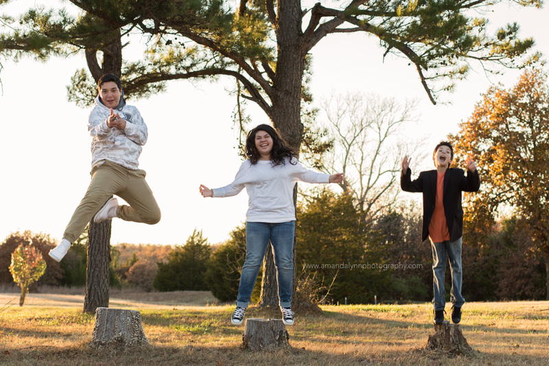 three kids jumping off tree stumps into the air in choctaw oklahoma