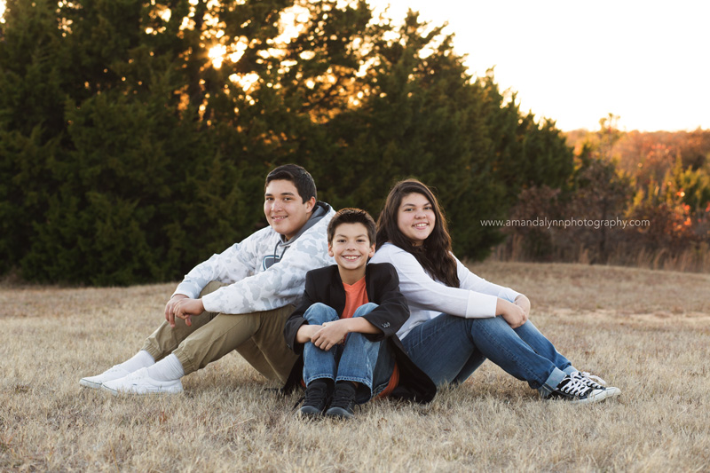 three kids sitting on grass in park in choctaw oklahoma