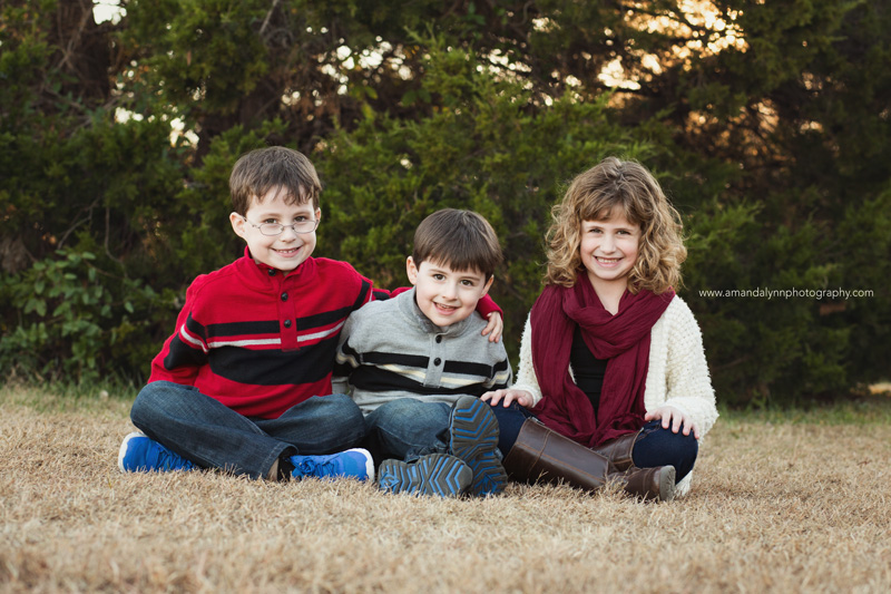 three siblings sitting on grass in Norman Oklahoma