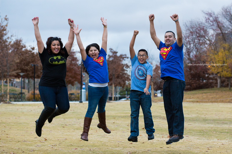 family jumping into the air wearing super hero tshirts at the myriad gardens in OKC