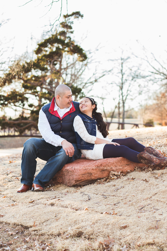 father and daughter sitting on rock at will rogers park in OKC