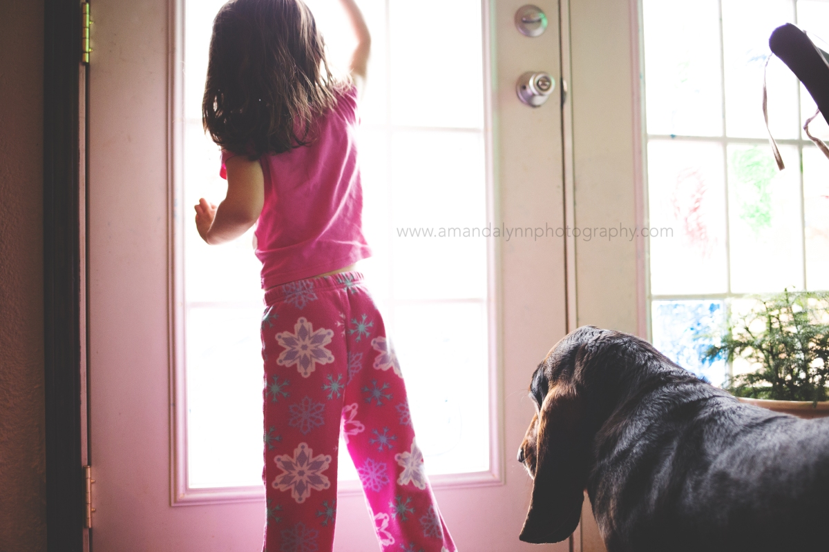 Little girl and basset hound look out door in harrah oklahoma