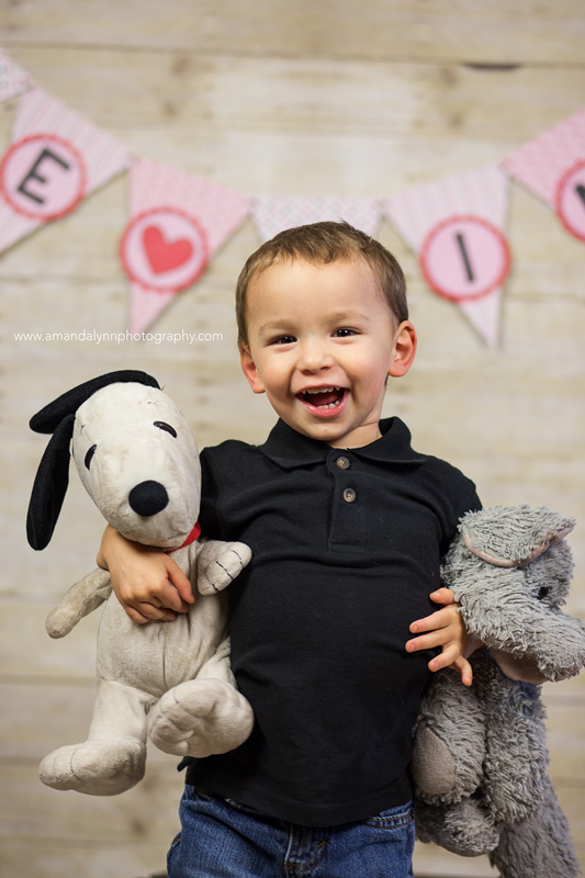 little boy with stuffed elephant and snoopy with Valentines props in harrah oklahoma