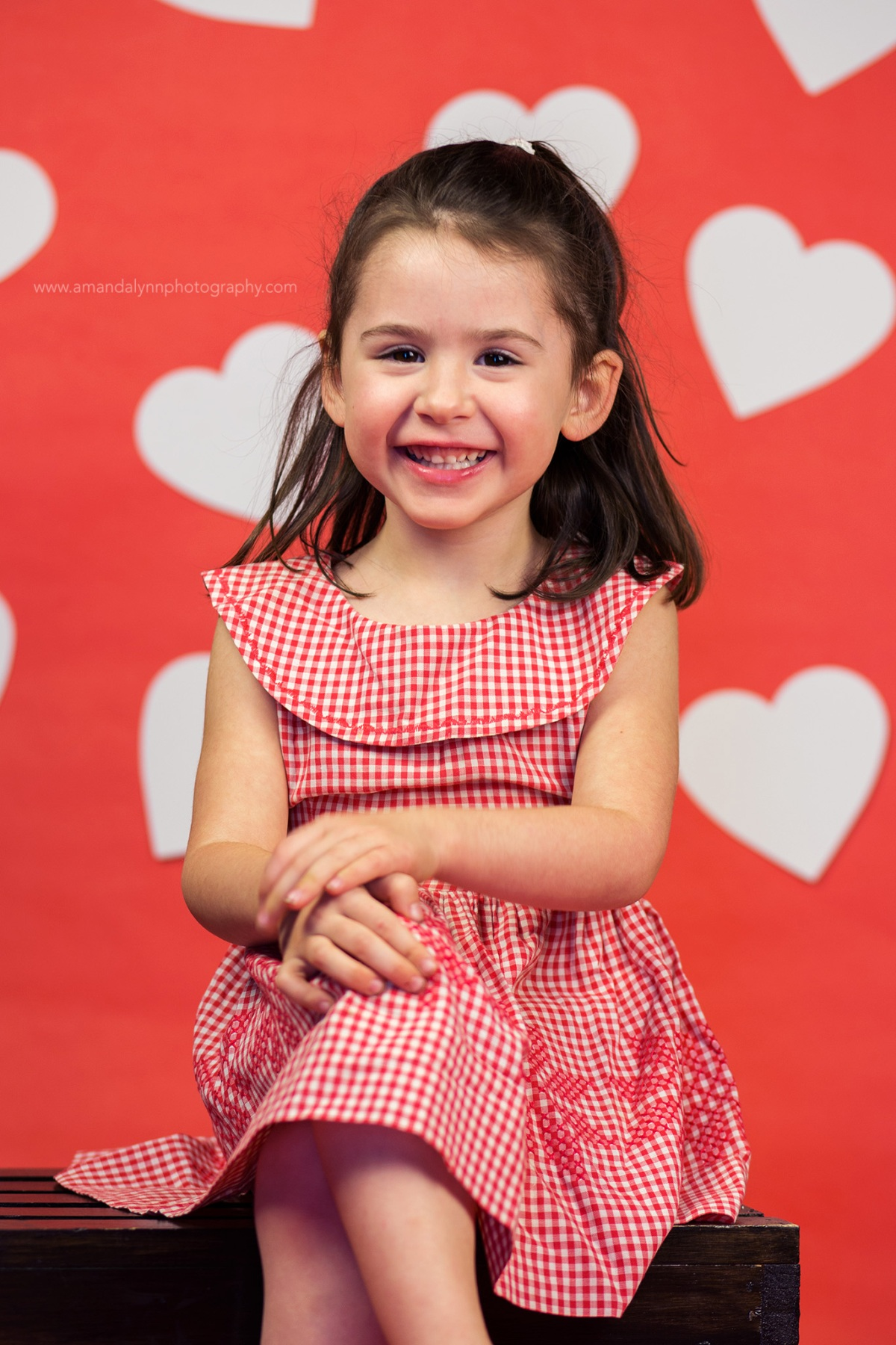little girl wears dress made by great grandmother with red backdrop and white hearts
