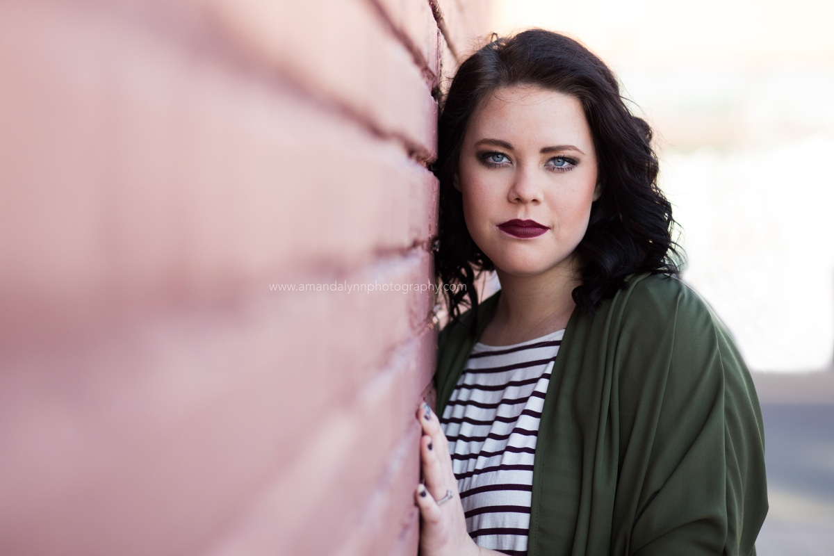 Senior Girl leaning against red brick wall at Automobile Alley in Oklahoma City