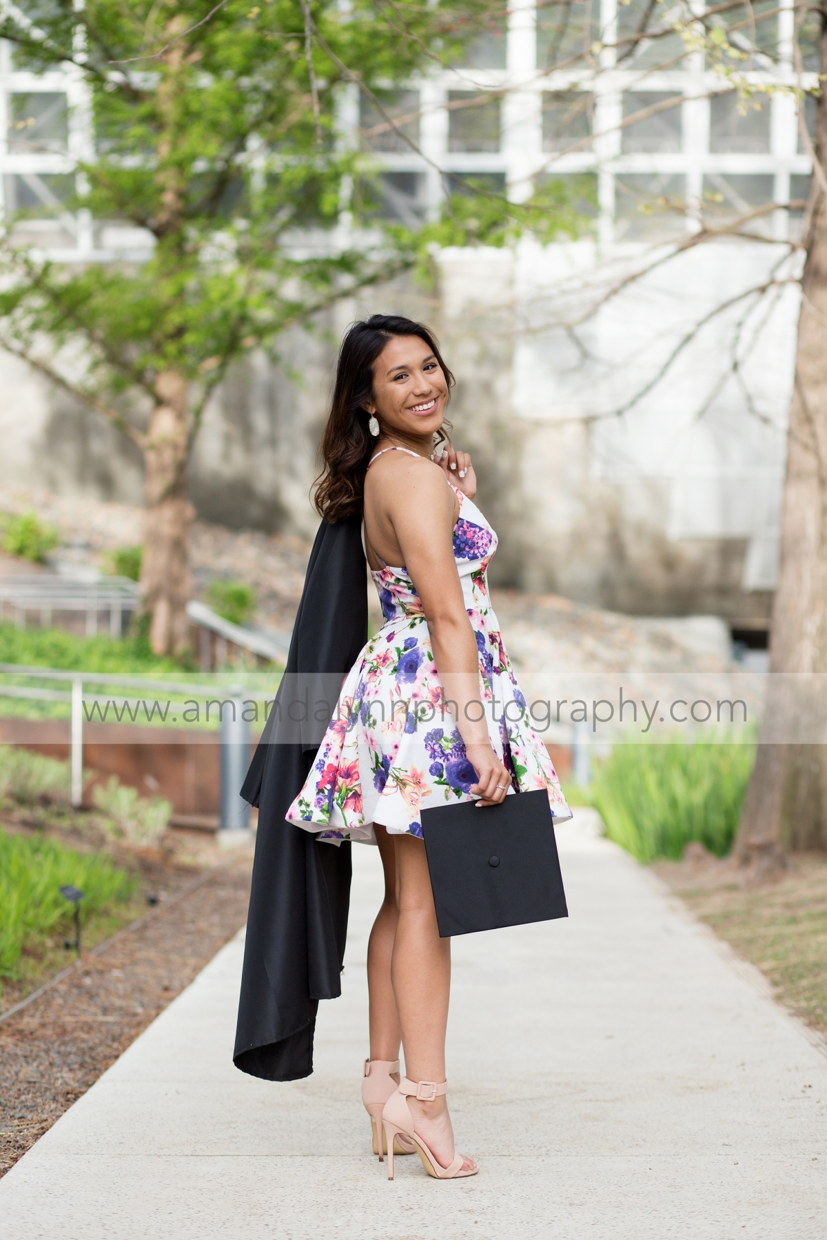 High School Senior Girl holding cap and gown at myriad gardens in oklahoma city