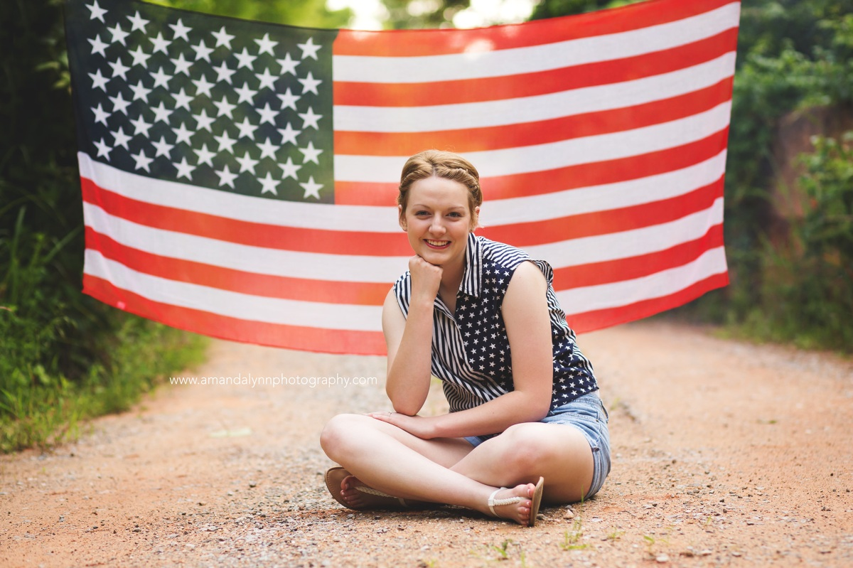 2017 Senior Rep for Amanda Lynn Photography Oklahoma City sitting on dirt road in front of American Flag