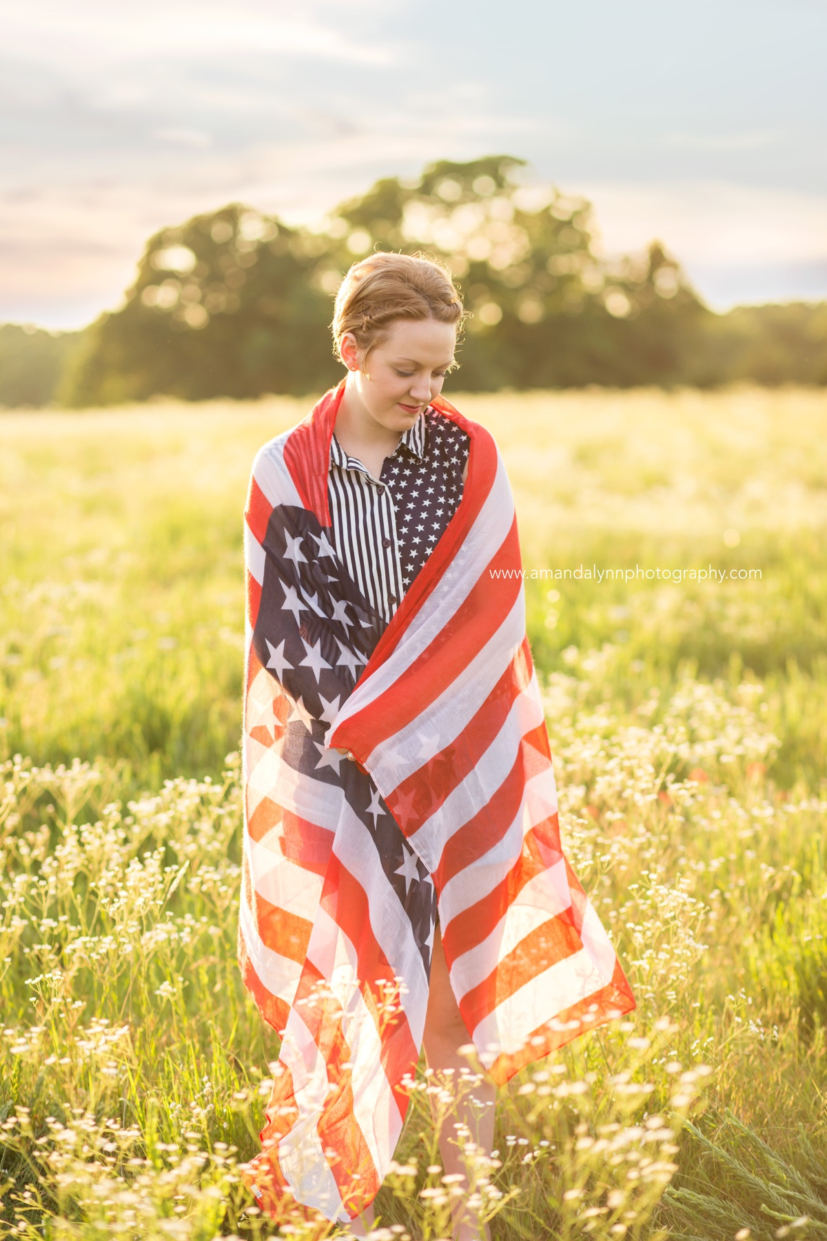 2017 Senior Rep for Amanda Lynn Photography Oklahoma City standing in a field of flowers with the American flag