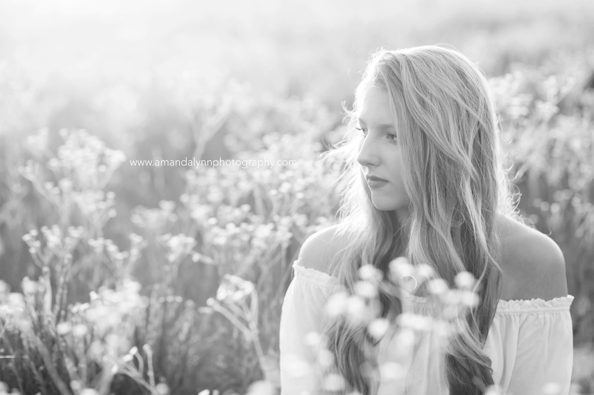 Black and White of 2017 Senior Rep for Amanda Lynn Photography Oklahoma City sitting in a field of flowers