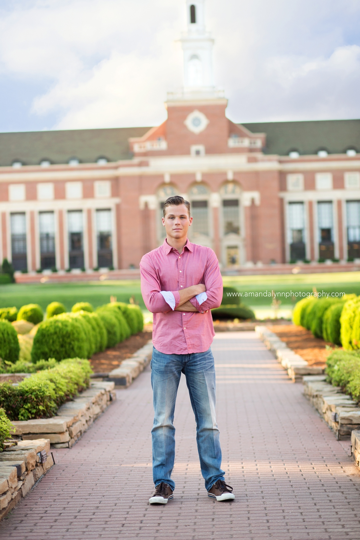 College graduate wearing pink shirt standing in front of library on OSU campus Oklahoma Photographer 2016