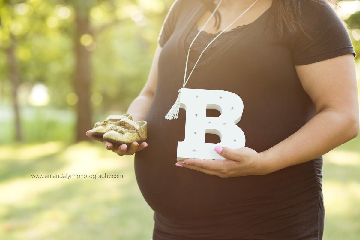Upclose photo of woman holding baby shoes at a Maternity Photoshoot at Will Rogers Park in Oklahoma City 2016