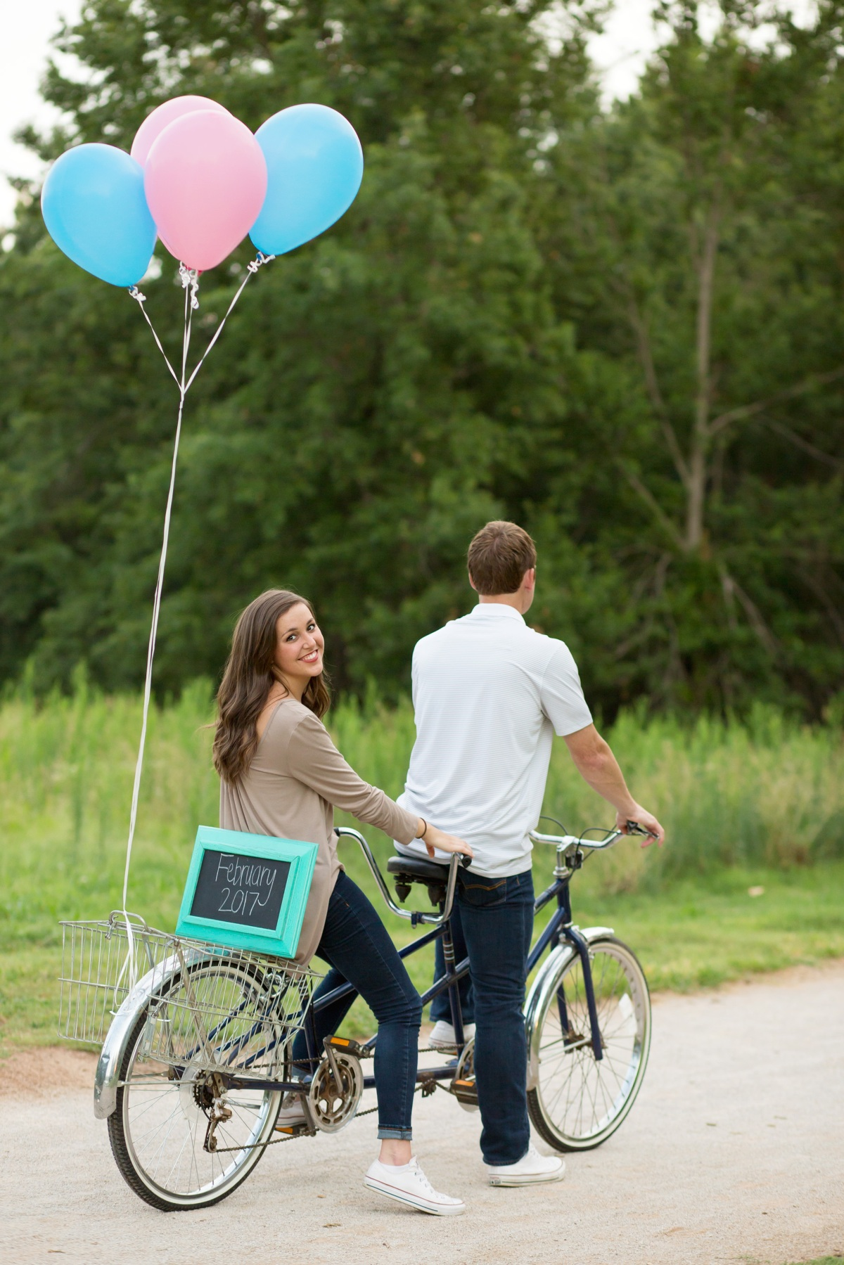 Couple riding bike with balloons at Baby Announcement Photoshoot in Stillwater, Oklahoma July 2016