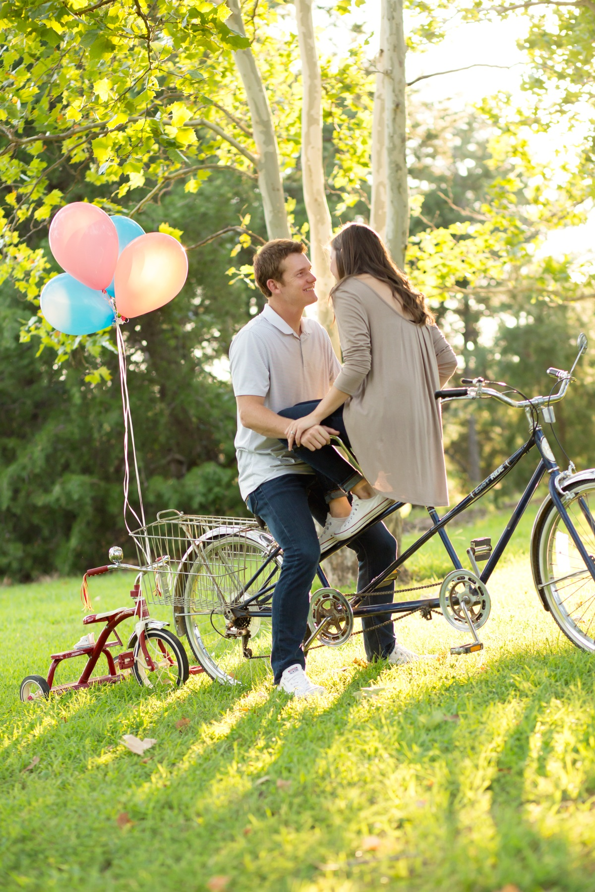 Couple sitting on bike with balloons at Baby Announcement Photoshoot in Stillwater, Oklahoma July 2016