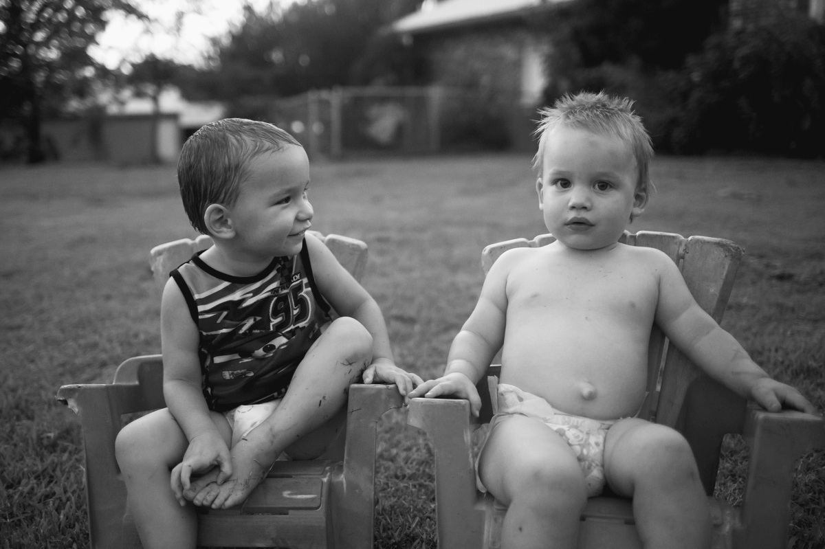 black and white of cousins sitting in chairs outside in harrah oklahoma 2016