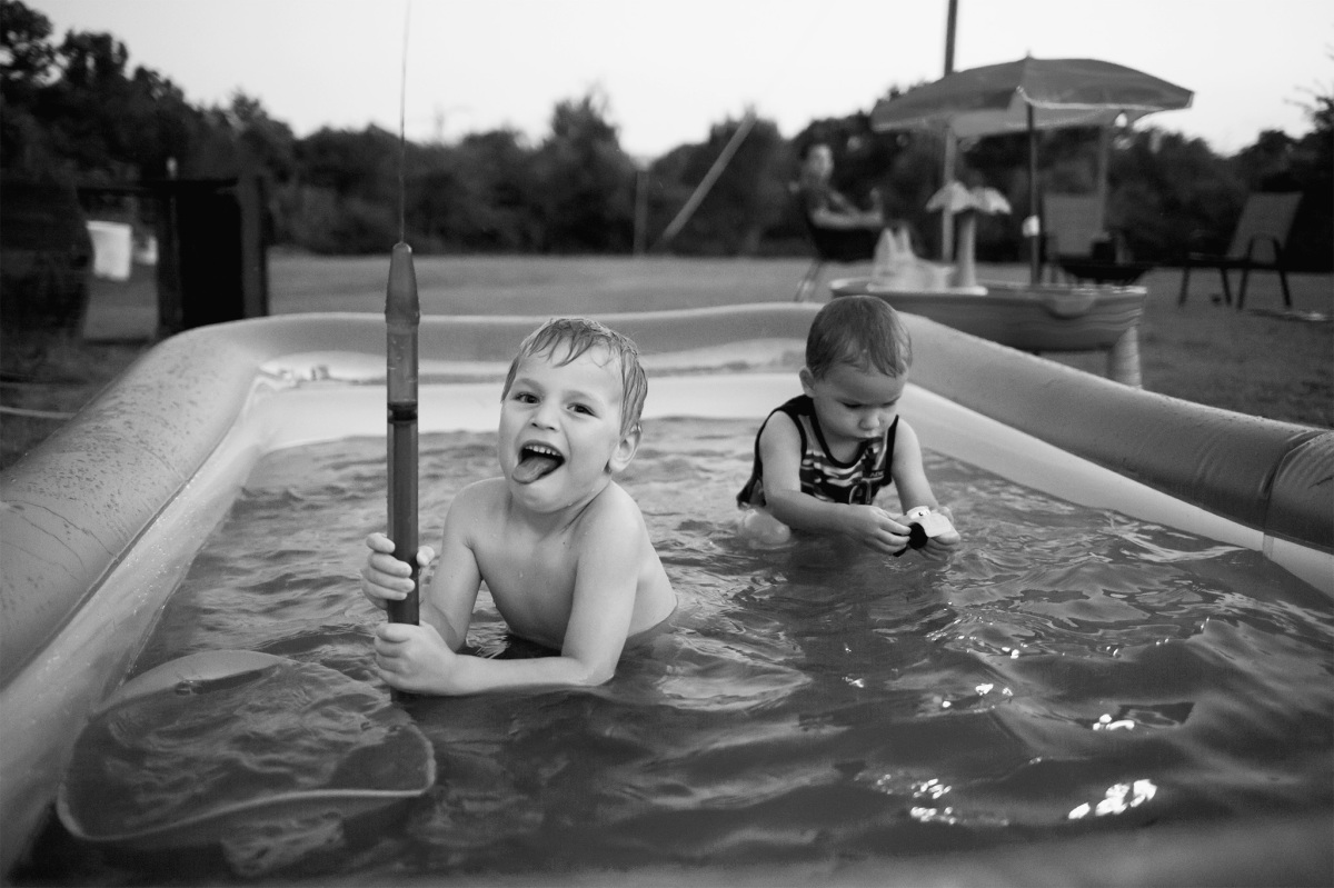 black and white of little boy playing in swimming pool in harrah oklahoma 2016
