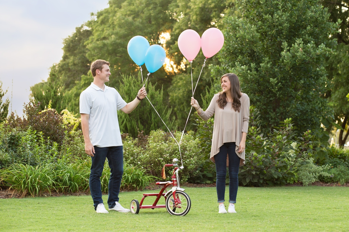 Couple holding balloons with little bicycle at Baby Announcement Photoshoot in Stillwater, Oklahoma July 2016