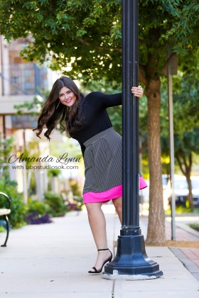 senior girl wearing skirt and high heels swinging around light pole oklahoma city