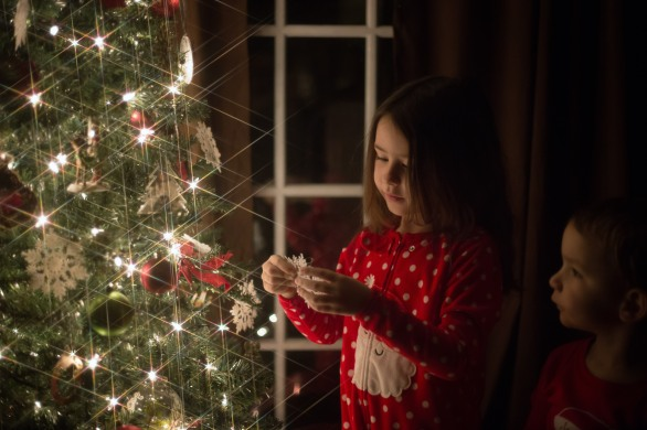 little girl wearing red christmas pajamas holding snow flake ornament next to christmas tress
