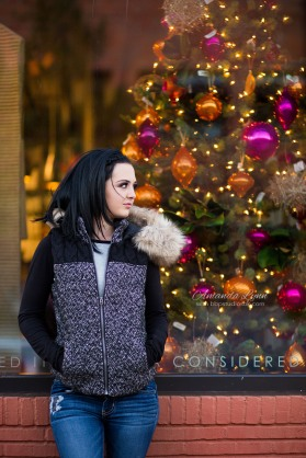 high school senior girl wearing winter coat standing in front of window with christmas tree in oklahoma city