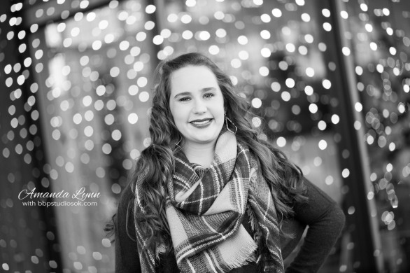 black and white of high school senior girl wearing big scarf standing in front of christmas lights in oklahoma city