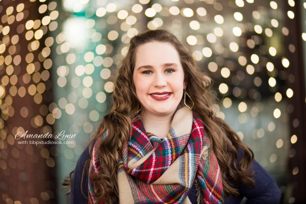 high school senior girl wearing big scarf standing in front of christmas lights in oklahoma city