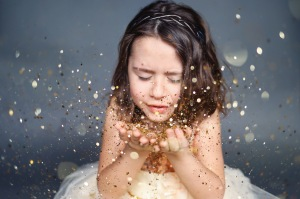 little girl wearing dress blowing gold glitter