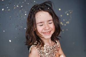 little girl wearing dress smiling surrounded by gold glitter